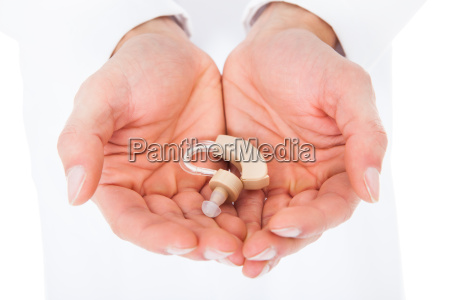 person holding hearing aid in cupped