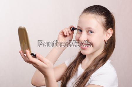 twelve year old girl paints eyelashes