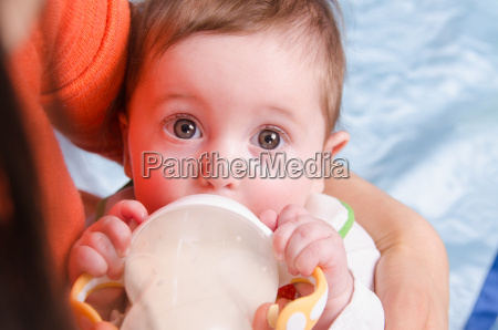 six month girl drinks milk from