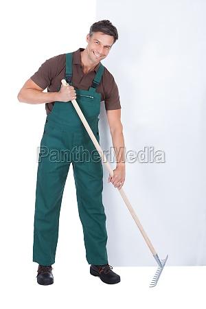 male gardener working with pitchfork