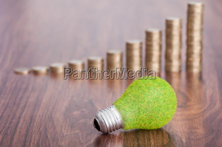 stack of coins with ecological bulb
