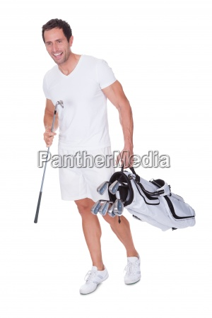 golf player holding bag with clubs