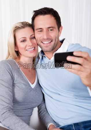 couple photographing themselves on a mobile