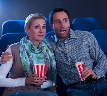 couple watching a movie reacting in
