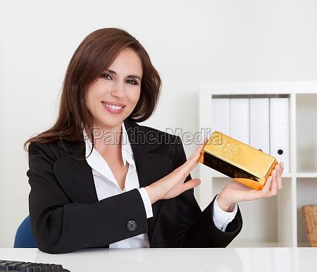 businesswoman holding gold bar