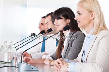 business people speaking in microphone