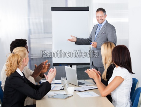 businesspeople clapping for a man in