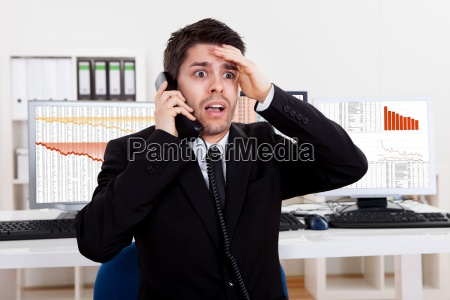 worried stock broker on the phone