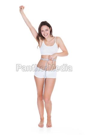 mujer emocionada midiendo su cintura