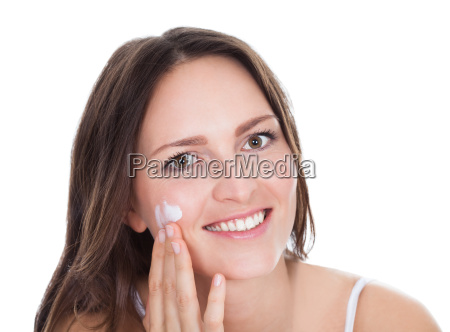 woman with moisturizer cream on finger