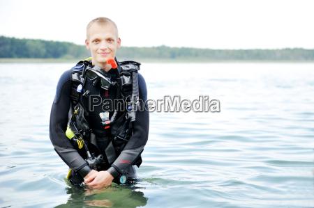 diver in diving equipment in water