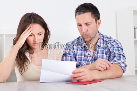 worried couple reading paper