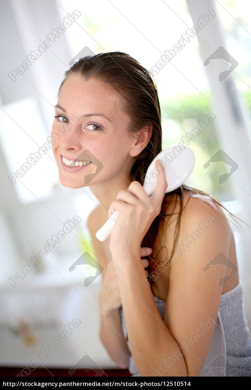 portrait, of, smiling, girl, brushing, her - 12510514