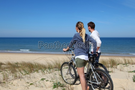 couple standing on a sand dune