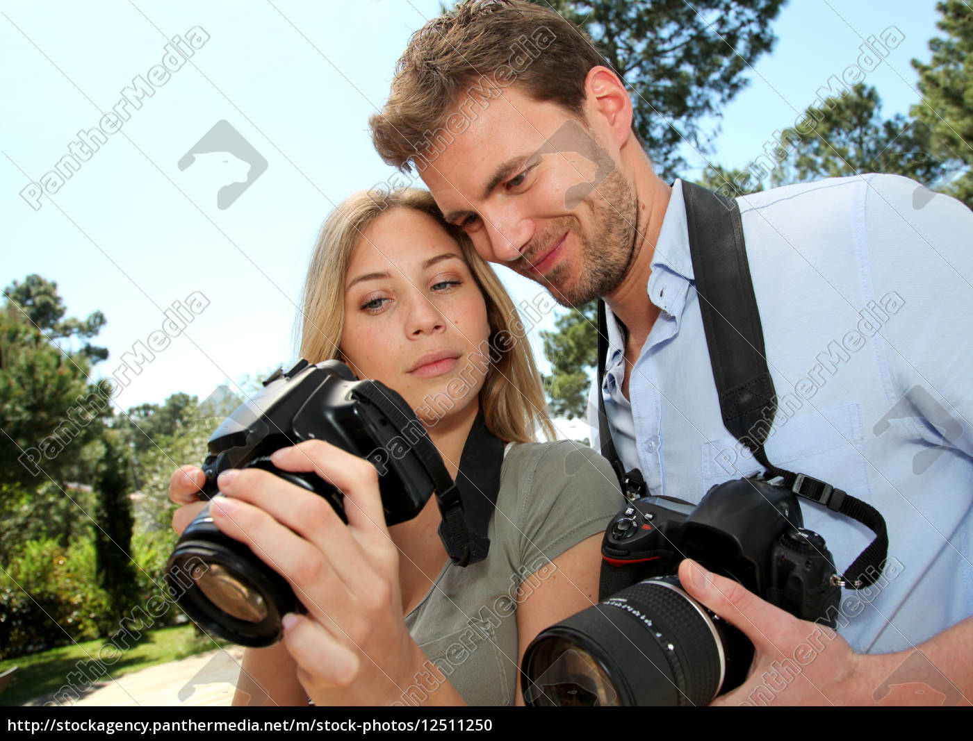 couple, looking, at, pictures, through, camera - 12511250
