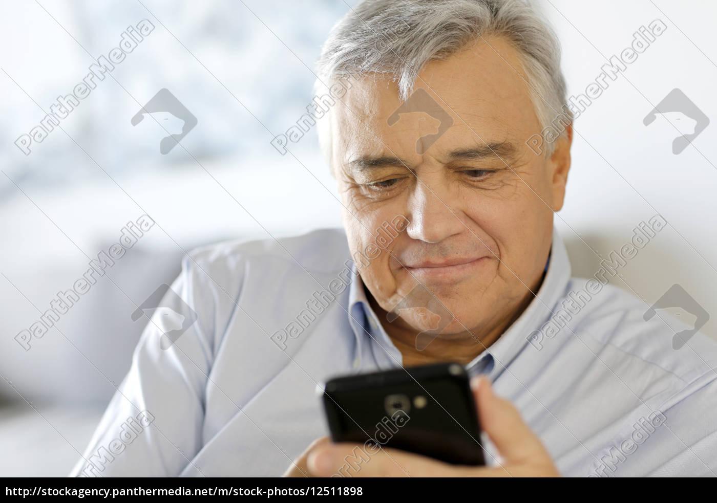portrait, of, senior, man, using, smartphone - 12511898