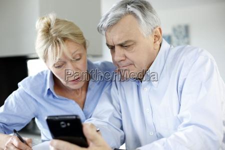 senior couple calculting bills amount using