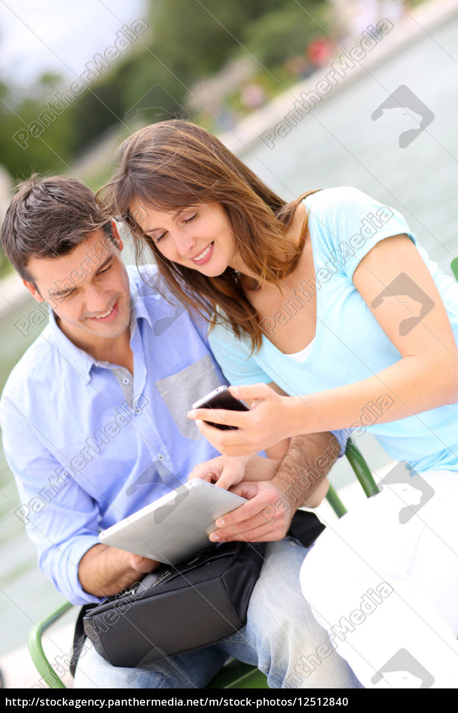 couple, using, tablet, and, cellphone, in - 12512840
