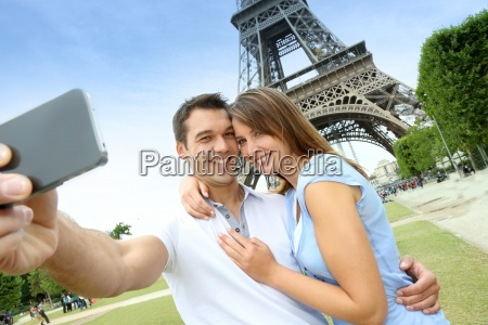 couple in paris taking pictures in