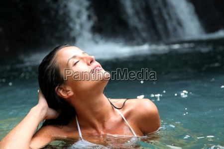 beautiful woman enjoying bathing near natural
