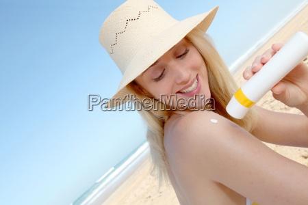 portrait, of, beautiful, woman, applying, sunblock - 12513200