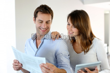 couple reading news on newspaper and