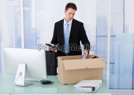 businessman collecting office supply in cardboard