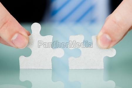 businessman joining puzzle pieces