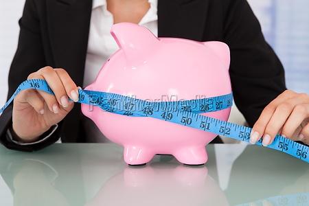 businesswoman measuring piggybank at desk