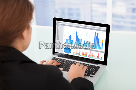 businesswoman, watching, financial, charts, on, laptop - 12527280