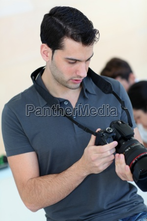 young photographer selecting photographies from shooting
