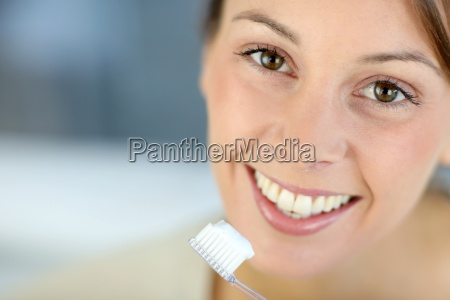 closeup on womans toothy smile brushing