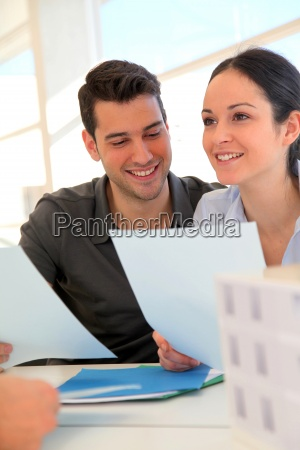 happy, young, couple, signing, property, purchase - 12528556