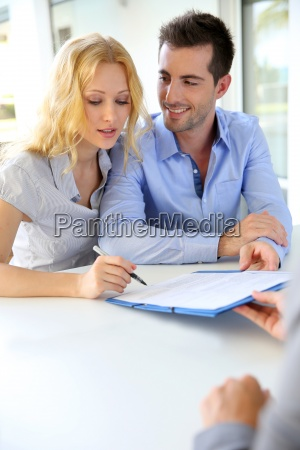 cheerful, couple, signing, property, contract, with - 12531120