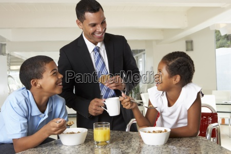 father having breakfast with children before