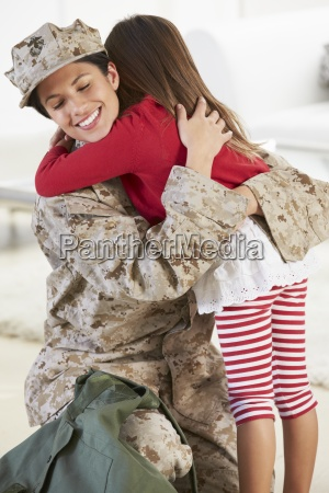 daughter greeting military mother home on