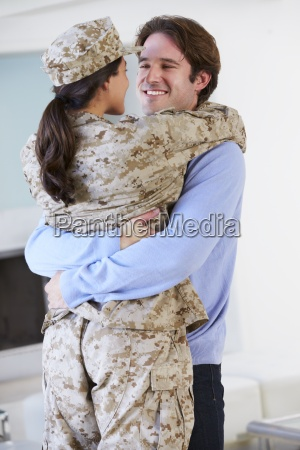 husband greeting military wife home on