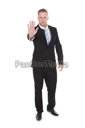 businessman holding up his hand in