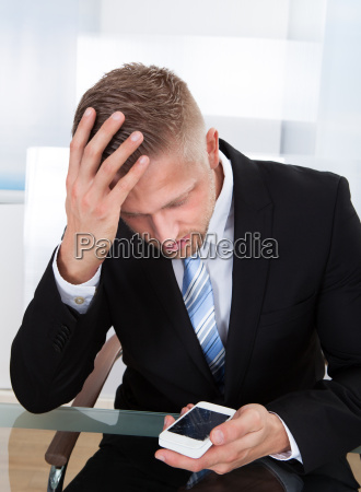 worried businessman checking a mobile message