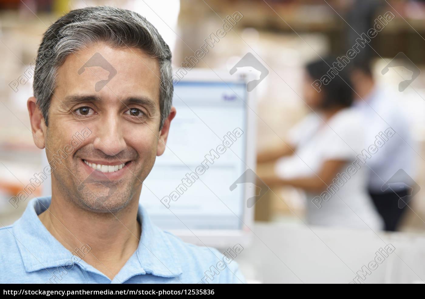 man, at, computer, terminal, in, distribution - 12535836