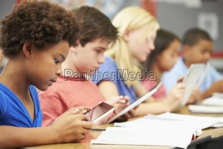 pupils in class using digital tablet
