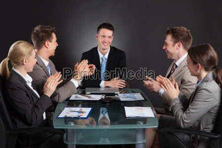 business people applauding for male colleague