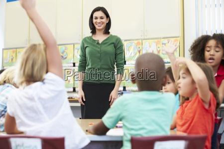 teacher, talking, to, elementary, pupils, in - 12536180