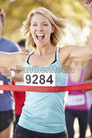 female runner winning marathon