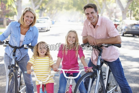 family cycling on suburban street