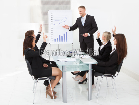 businesspeople answering businessman in meeting