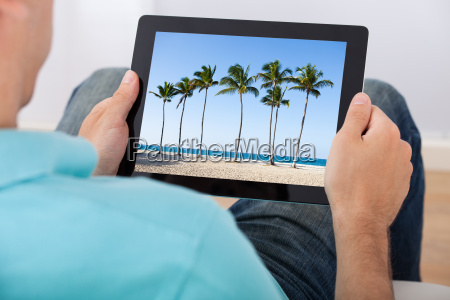 man looking at beach photo on