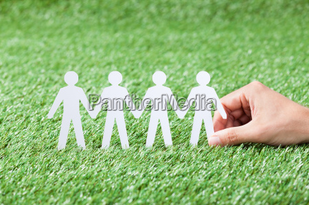 hand holding paper people chain on