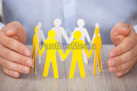 hands protecting team of paper people