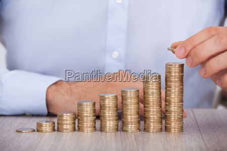 businessman stacking euro coins at desk